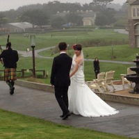 A bagpiper and a bride and groom.
